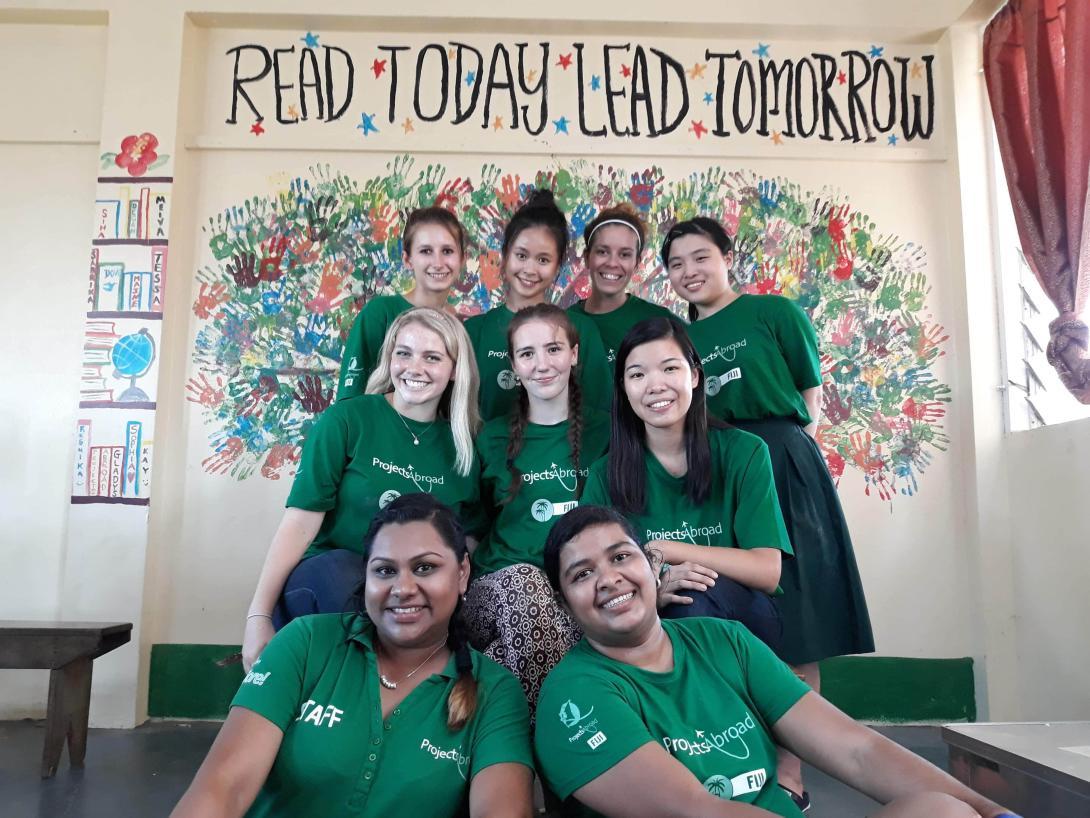 Estudiantes en un voluntariado para adolescentes en verano posando después de terminar un mural para promover la lectura en Fiyi.